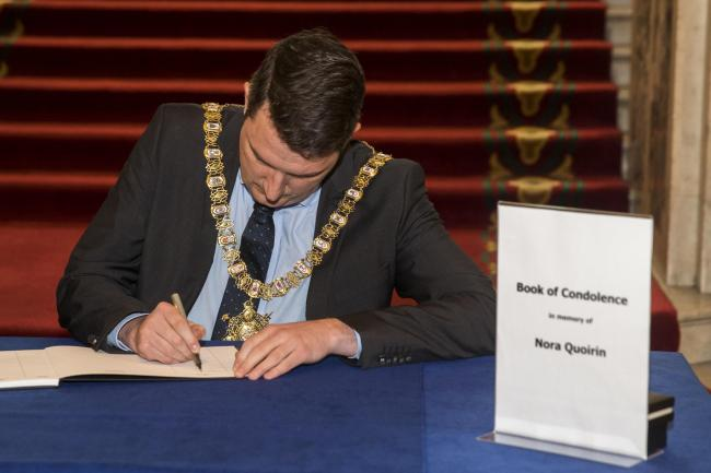 John Finucane signs the book of condolence