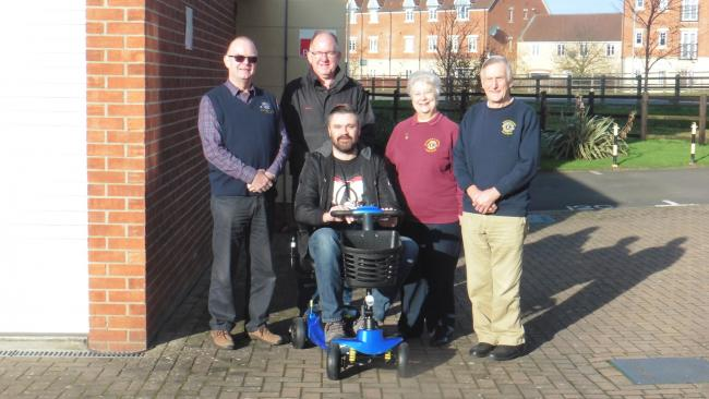 DONATION: David Atkins, Steve Cutler, Brenda Beer and Colin Rufus present Chris Annis with his new scooter