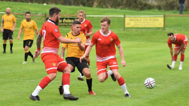 Porthleven striker Dan Quirke (centre) receives close attention from two Wadebridge men