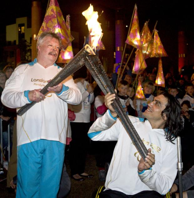 Simon Weston (left) and Nazim Erdem with the Welsh National Flame during the parade to the evening celebration site, Cardiff.