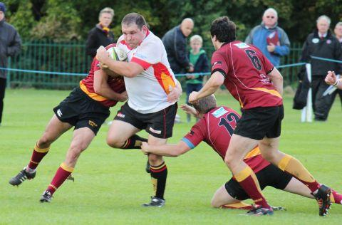 James Bryant (white shirt) charges past two tacklers. PHOTO: David Pomeroy