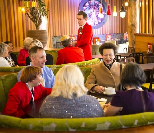 Princess Anne laughs and chats with carers and Redcoats at Butlin's.