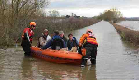 stock image: villagers are helped by boat crews in Muchelney