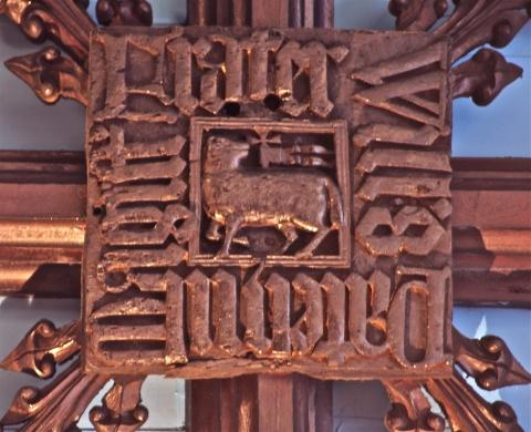 The Latin inscription surrounds the figure of a lamb, looking backwards at a staff with a cross and two pennants - the symbol of St John the Baptist. Photo: Dr P E Cattermole.