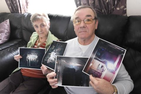 Vi and Leslie Davies with photos showing the extent of the damage caused by the fire.
