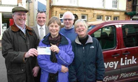 David Impey and Bruce Keay of Wiveliscombe and District Rotary Club present a cheque for £1,000 to volunteer drivers Sue Tyrie, Richard Harding and Sarah Cochrane.
