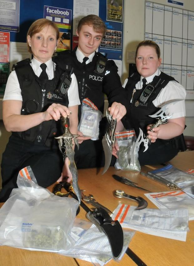 Officers at Bridgwater police station with some of the confiscated knives, drugs and money