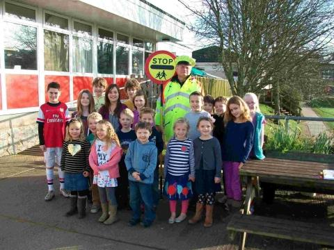 Some of the pupils at Parc Eglos Primary School wishing lollipop man Frank Timmins well in his retirement