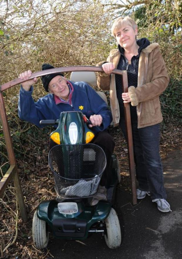 Cllr Jenny Kenton with mobility scooter user Sam Welch, 85, with the problem barrier which has since been removed
