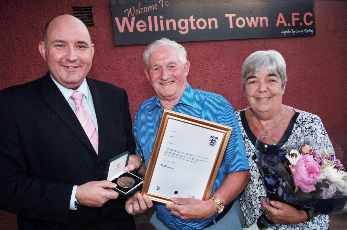 Tony Bull, centre, receives his presentation and medal from the Football Association in 2010, with wife Janet, right.
