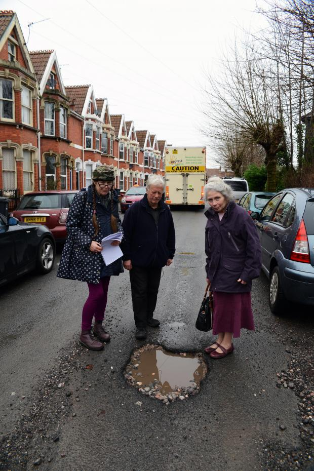 This is The West Country: Anne Heritage, Roy Franklin and Sue Blackmore stand by their street's giant pothole.