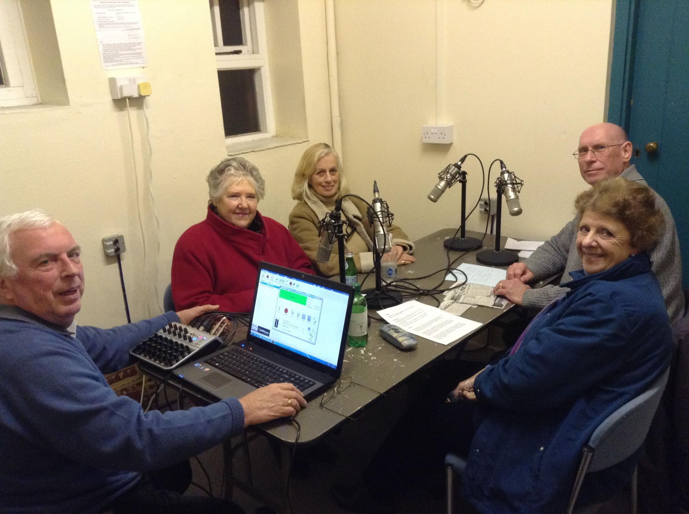 The crew pack into the small recording studio to read out articles from the Mercury