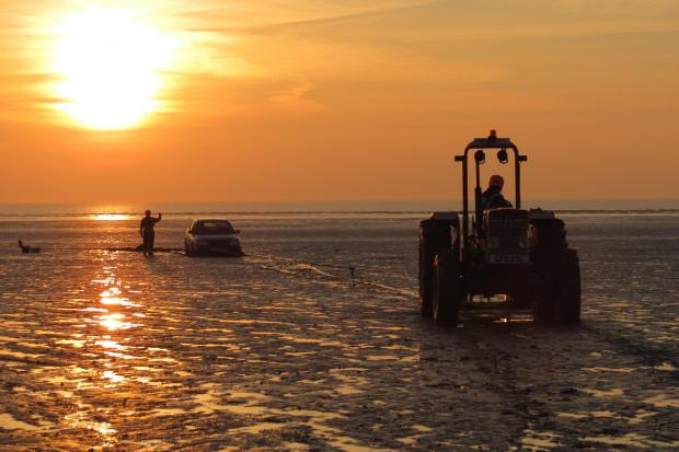 A BARB tractor pulls the car on Brean beach to safety