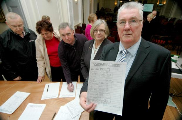RESIDENTS and councillor Christine Lawrence support hotelier Bryan Leaker (front) by signing a petition. PHOTO: Paul Courtney.