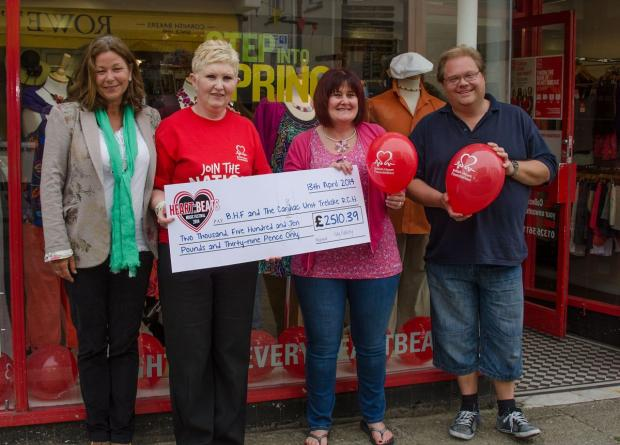 Cardiac catheter lab manager at the hospital Tina Prestwood and British Heart Foundation shop manager Tina Altree are presented a cheque from festival organisers Kay Harvey and Graham Baumbach.