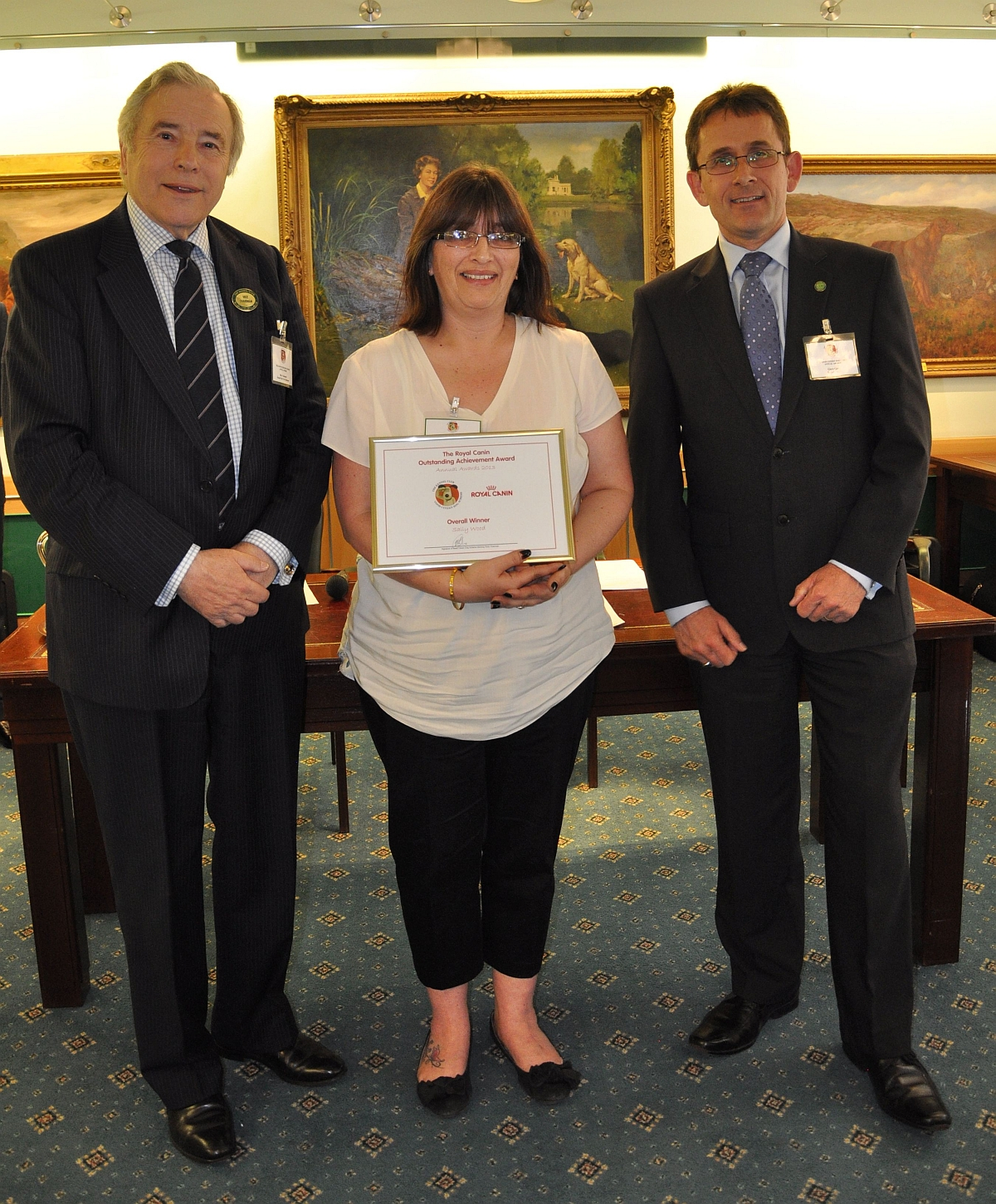 Sally Wood, centre, is pictured collecting her award from Kennel Club vice chairman Mike Townsend, left, and Gary Gray from Royal Canin.