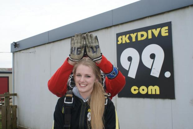 Laurenn Chappel before her skydive as her instructor stands behind her with a cheeky message
