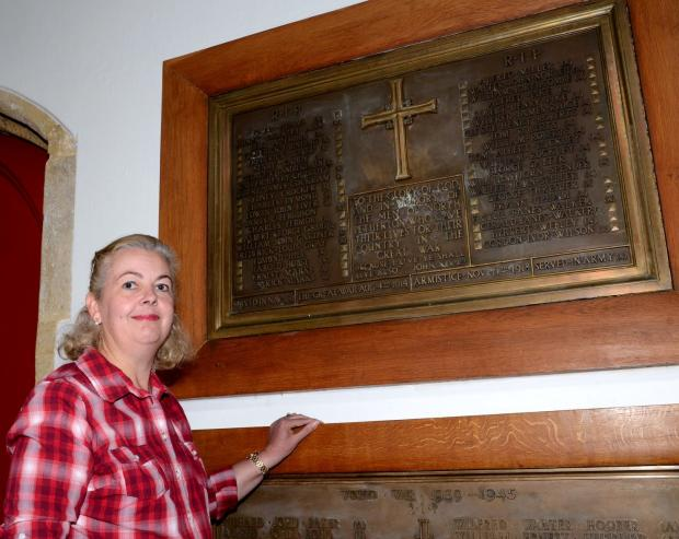 Wendy Mclean stands beside the war memorial plaque at North Petherton