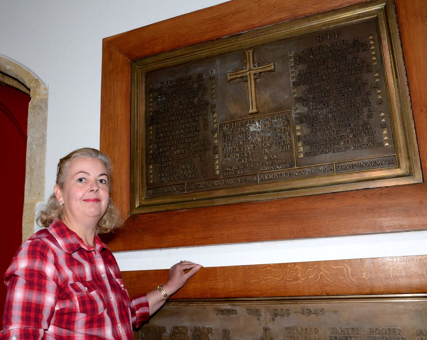 Wendy Mclean stands beside the war memorial plaque at North Petherton's Sty Mar