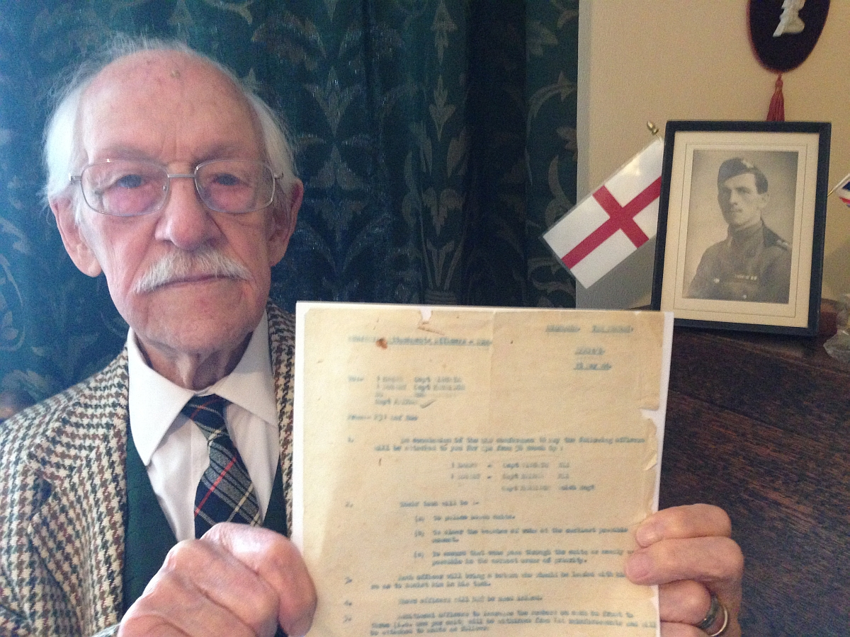 Lewis Haines holds up the order served on him ahead of the Battle of Normandy.