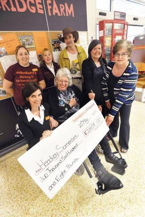 Representatives of Headway Somerset receive a cheque for £2,608 from staff at Sainsbury's.