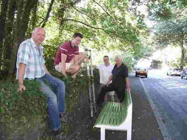 Shaun Davie (far left) and other Friends of Falmouth Bay recovering the bench.