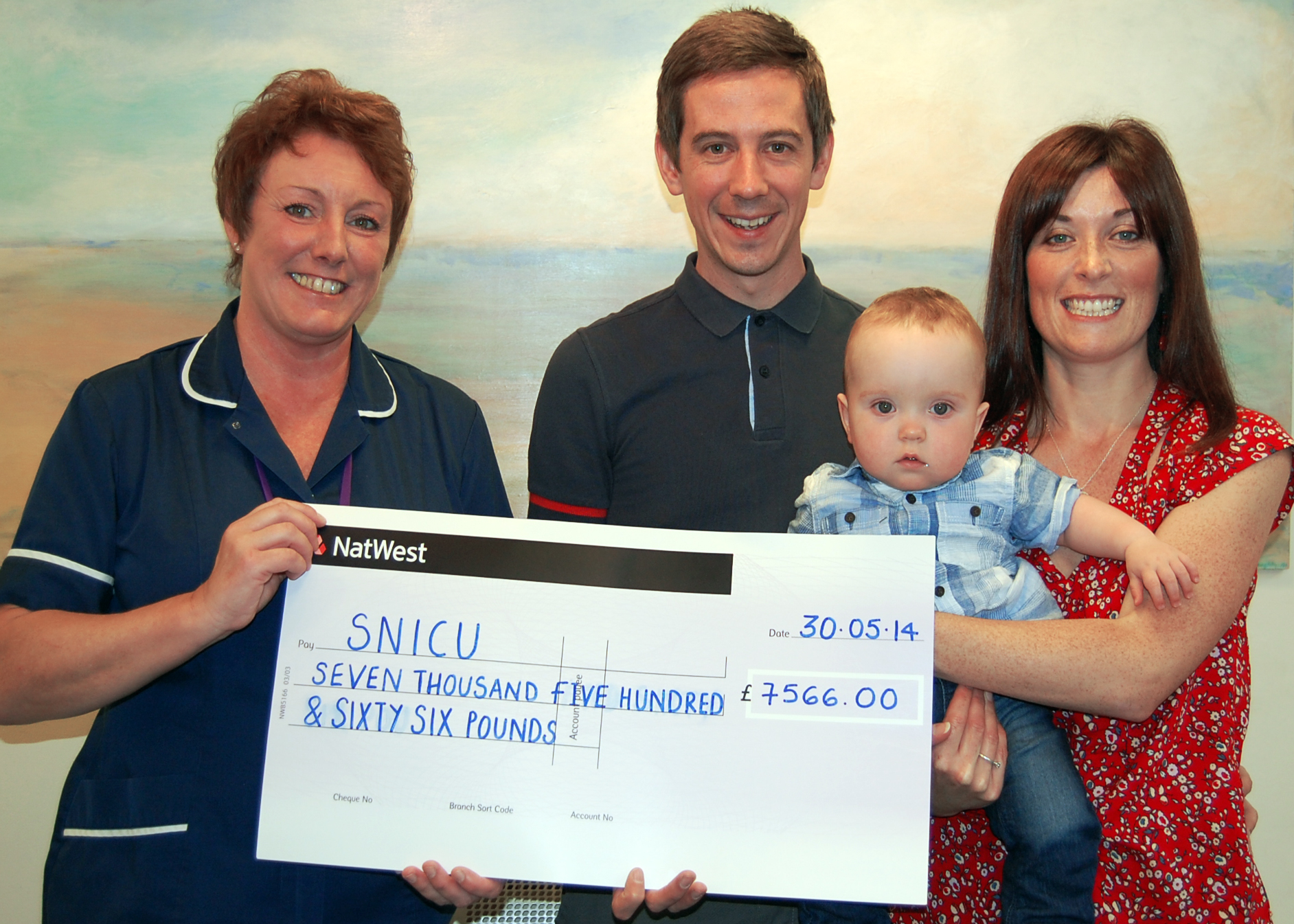 MICK, Louise and baby Samuel present the charity cheque for an amazing £7,500 to ward manager Sue Spooner.