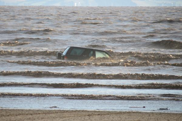 The Vauxhall Frontera was engulfed by the sea after becoming stuck in mud in a 'vehicle free zone' on Brean beach last Tuesday. Photo: BARB.
