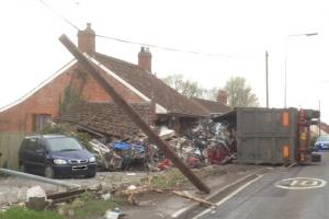 CRASH: The lorry overturned has caused severe damage to a nearby house
