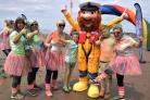RAINBOW RACE: Runners at last year's RNLI race cheer after crossing the finish line . Credit Mike Lang