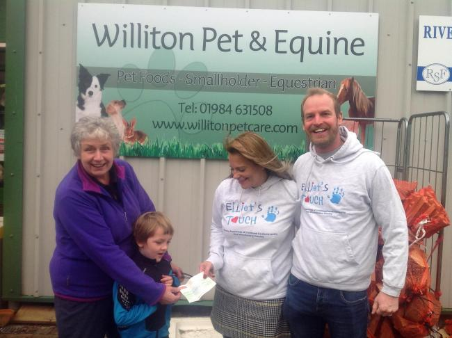 SUPPORT: Wendy Berry, owner of Williton Pet and Equine, with her grandson Hugo Poole(Aged 5) handing over cheque to Elliot's Touch Founders Donna and Paul