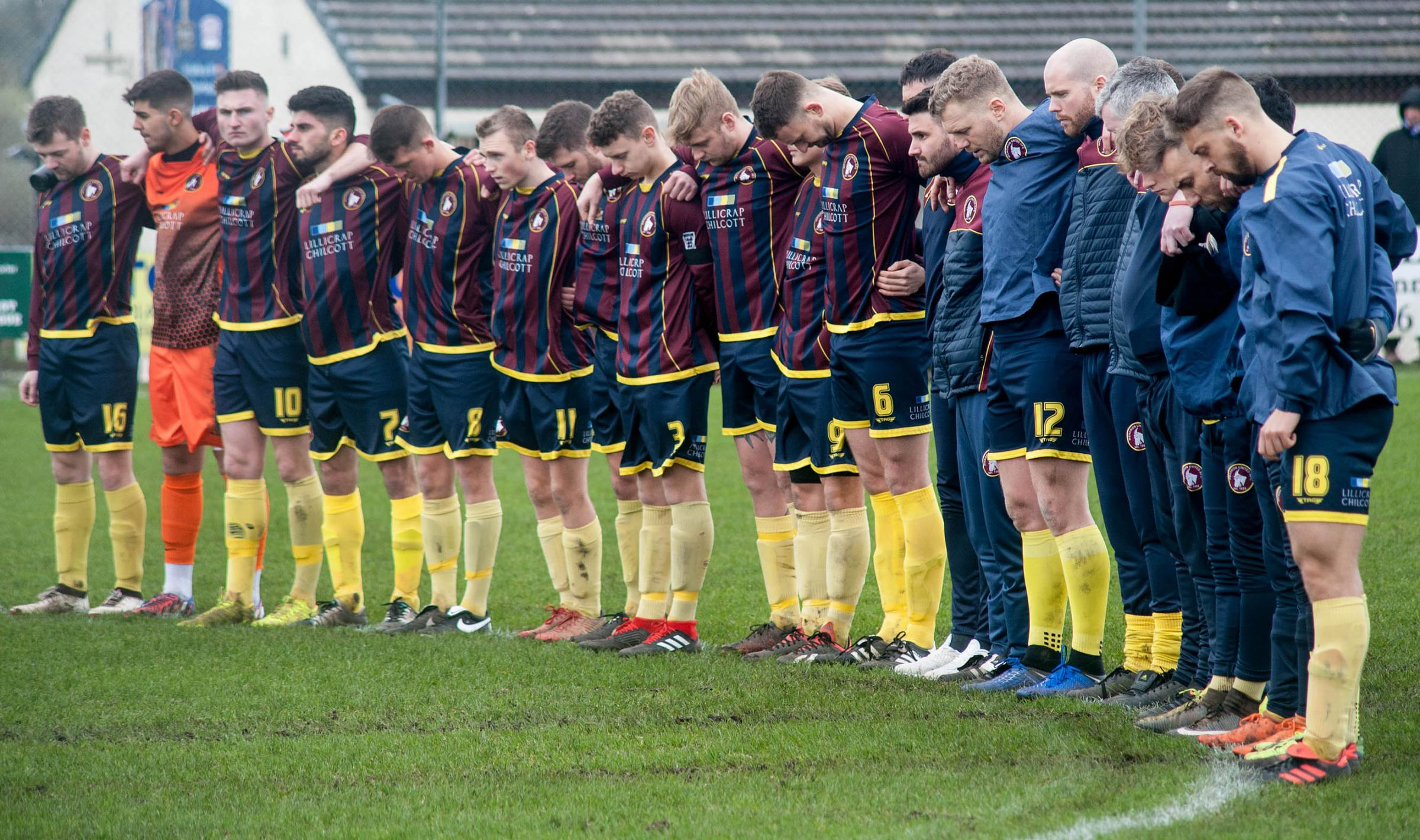 Wendron United players and coaching staff observe the minute's silence before kick-off on Saturday. Picture by Colin Higgs