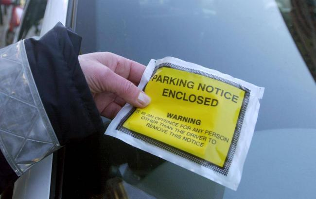 File photo of a parking ticket being placed on a car in Cumbria by a county council traffic warden.